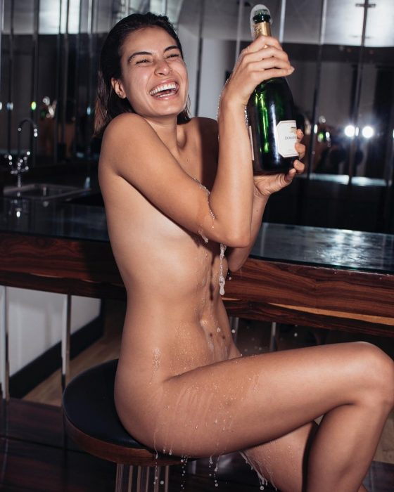 Cheerful model Milena Gorum nude with a big bottle of champagne