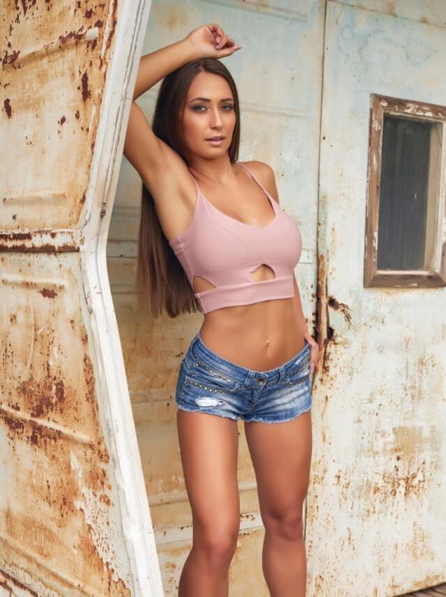 Busty brunette in sports bra and jean shorts